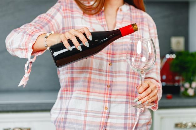 Nicht erkennbare frau, die rotwein in eine glasnahaufnahme gießt