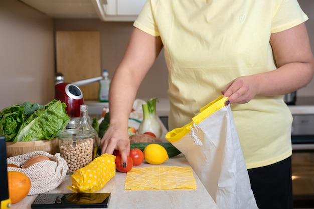 Nicht erkennbare frau im gelben t-shirt, das gemüse in umweltfreundliche baumwolltasche legt. null abfall und nachhaltiger lebensstil