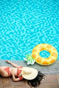 Nicht erkennbare frau in roter badebekleidung, die mit gesichtsbedecktem sommerhut in der nähe des swimmingpools schläft