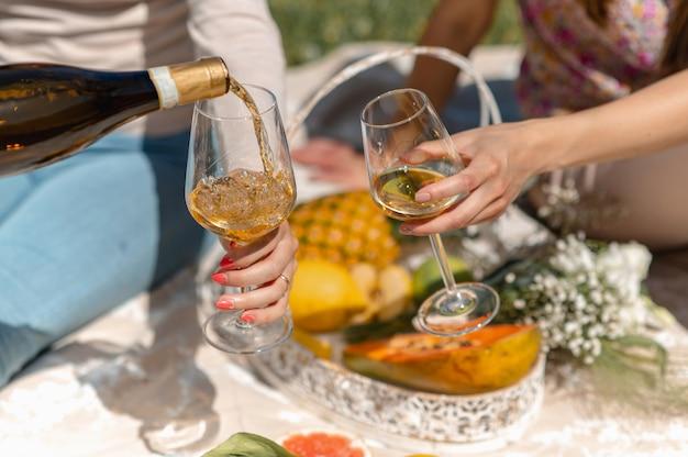 Nicht erkennbare frauen, die auf einer decke sitzen und picknick machen. frau gießt weißwein in ein glas. tropische früchte im hintergrund