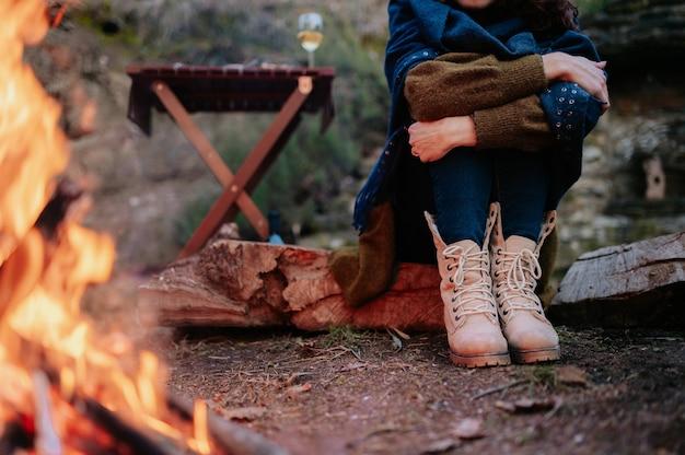 Nicht erkennbare frauenbeine, die während eines winterpicknicks neben einem feuer sitzen.