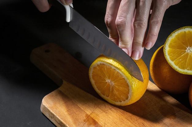 Nicht erkennbare frauenhände, die frische gesunde orangenscheiben auf holzbrett schneiden