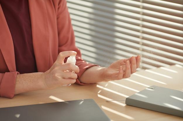 Nicht erkennbare geschäftsfrau, die hände mit desinfektionsmittel am arbeitsplatz besprüht, der durch sonnenlicht beleuchtet wird