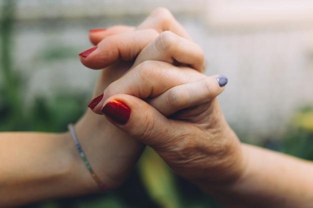 Nicht erkennbare großmutter und ihre enkelin, die mit liebe hand in hand halten