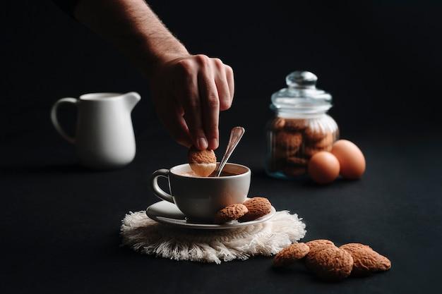 Nicht erkennbare hand, die einen keks in heißen kaffee taucht. schließen sie oben. kaffeetasse mit einigen keksen in einem glas, milch in einer tasse und eiern.