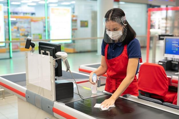 Nicht erkennbare kassiererin mit roter schürze, die die kassenoberfläche mit desinfektionsmittel in einem modernen geschäft reinigt