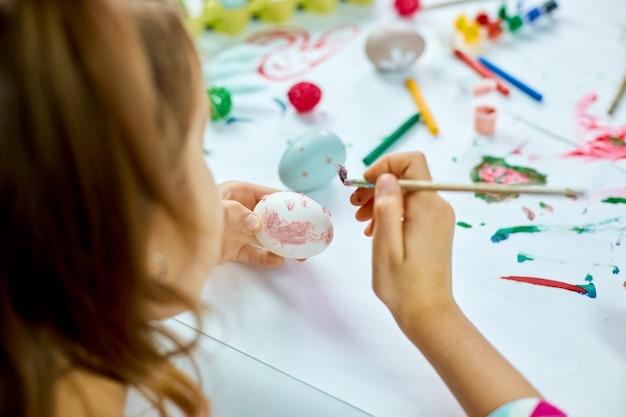 Nicht erkennbare kleine mädchenmalerei, zeichnung mit bürsteneiern zu hause. kind bereitet sich auf ostern vor, hat spaß und feiert fest. frohe ostern, diy