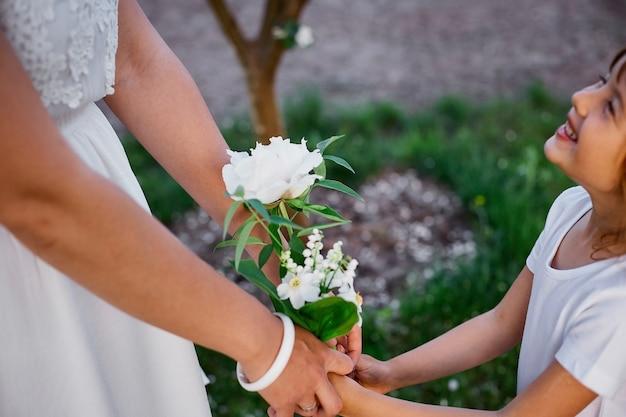 Nicht erkennbare mutter und tochter, die hände im blühenden frühlingsgarten händchen halten glückliche frau und kind, weiße kleidung im freien tragend, frühlingssaison kommt. muttertagsferienkonzept