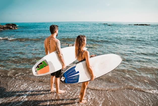 Nicht erkennbare paare mit den surfbrettern, die nahe wellenartig bewegendem meer stehen