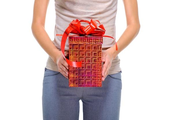 Nicht erkennbare person, die die große rote geschenkbox mit einem roten band hält