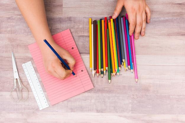 Nicht erkennbare person mit buntstift auf papier