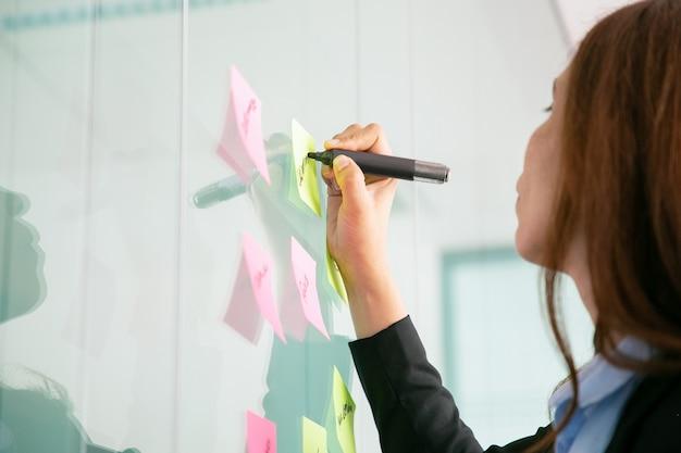 Nicht erkennbare rothaarige geschäftsfrau, die auf aufkleber mit markierung schreibt