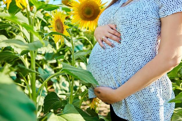 Nicht erkennbare schwangere frau, die bauch berührt