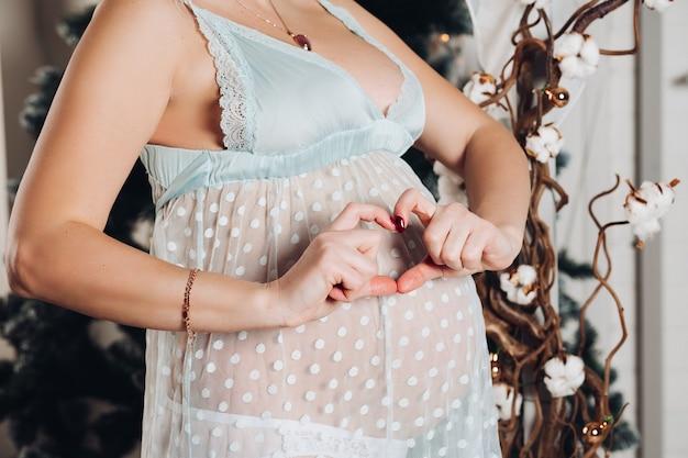 Nicht erkennbare schwangere frau mit den händen in herzform am bauch.