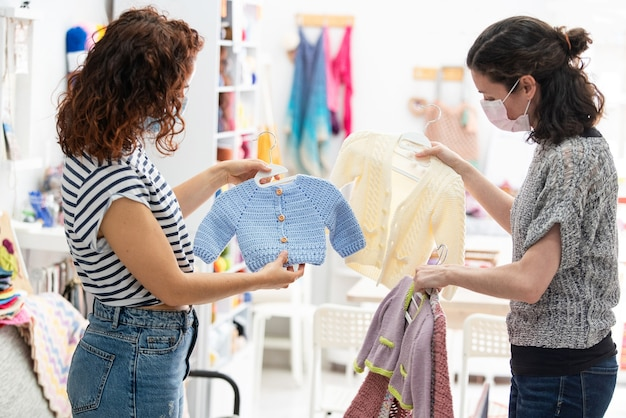 Nicht erkennbare schwangere junge frau, die mütterliche kleidung für ihr baby kauft