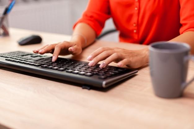 Nicht erkennbare unternehmerin, die finanzkommunikation am arbeitsplatz eingibt. beschäftigter erfolgreicher mitarbeiter, der am tisch am arbeitsplatz sitzt und an einem wichtigen finanzprojekt arbeitet.