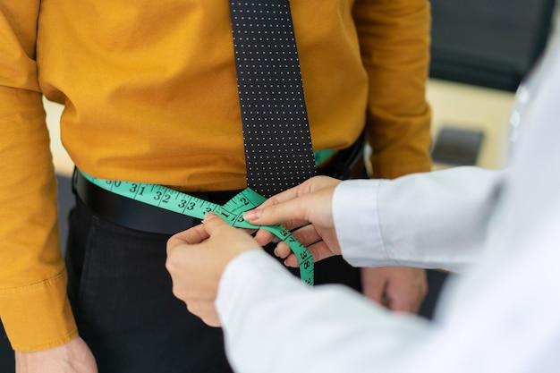 Nicht erkennbarer arzt, der die taille von fettleibigen männlichen patienten mit maßband misst, gesunde ernährung - gesundheitswesen und wellness bei berufstätigen. ernährungsberater maßnahme am bauch des mannes im krankenhaus.