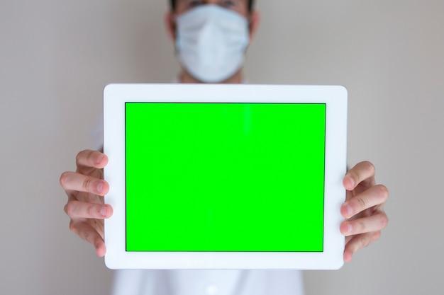 Nicht erkennbarer arzt, der eine tablette mit grünem bildschirm im krankenhaus hält.