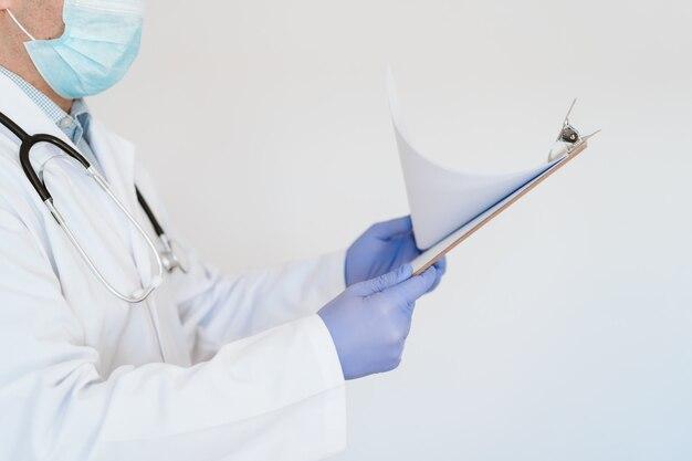 Nicht erkennbarer arzt mit schutzmaske und handschuhen
