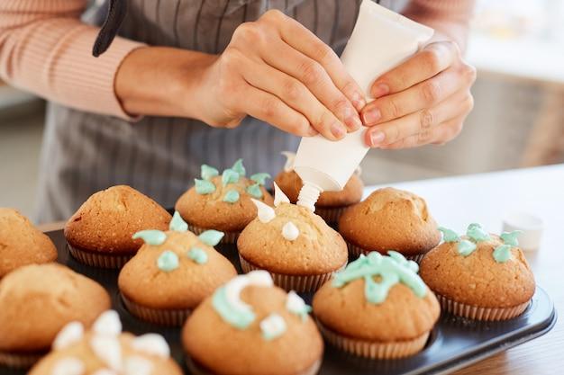 Nicht erkennbarer bäcker, der frische hausgemachte cupcakes mit süßer sahne verziert, horizontale nahaufnahme