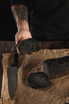 Nicht erkennbarer bäcker mit tätowierten händen zeigt ein stück frisch gebackenes hausgemachtes holzkohlebrot, großes hauptmesser in der nähe auf bastelpapier auf rustikalem holztisch zum verkauf bereit