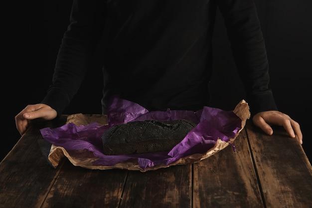 Nicht erkennbarer bäcker präsentierte frisch gebackenes luxuriöses hausgemachtes holzkohlebrot in violettem bastelpapier auf rustikalem holztisch