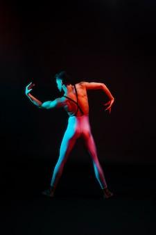 Nicht erkennbarer balletttänzer im trikotanzug mit gebogenen armen im scheinwerferlicht