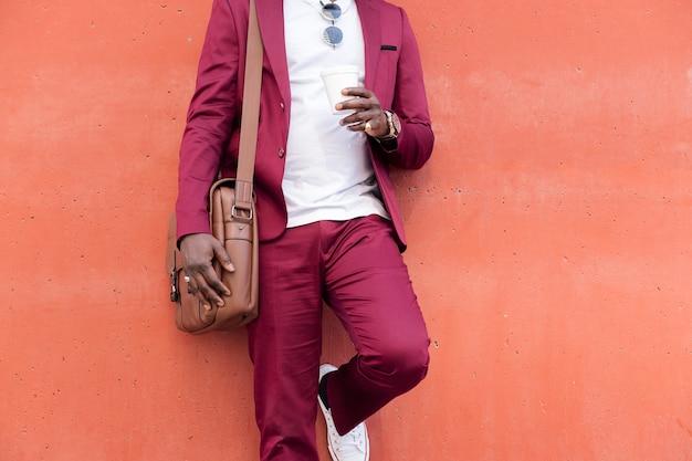 Nicht erkennbarer eleganter afrikanischer geschäftsmann in anzug mit aktentasche, der kaffee in der hand vor rotem hintergrund hält, platz für text kopieren copy