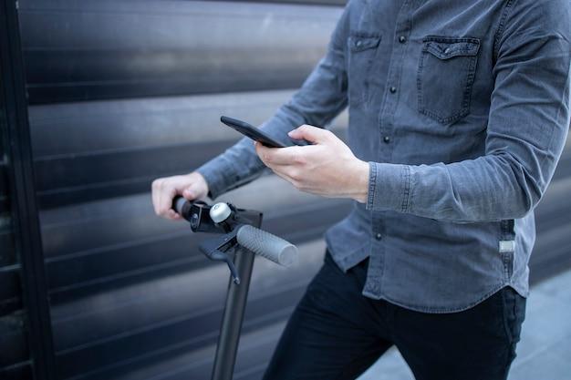 Nicht erkennbarer geschäftsmann, der app auf seinem smartphone benutzt, während er auf elektroroller steht