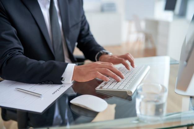Nicht erkennbarer geschäftsmann, der auf tastatur im büro schreibt