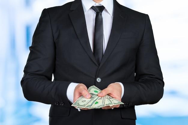 Nicht erkennbarer geschäftsmann zeigt dollarbanknote