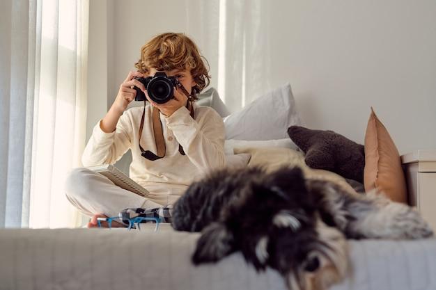 Nicht erkennbarer junge, der drinnen ein foto vor der kamera gegen flauschigen hund macht