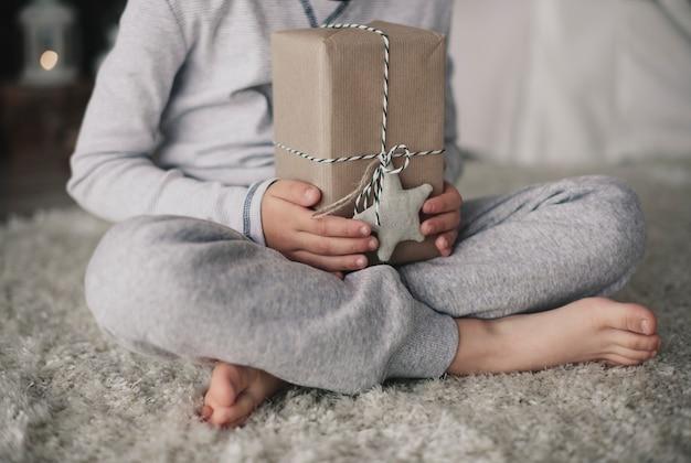 Nicht erkennbarer junge, der eine geschenkbox hält