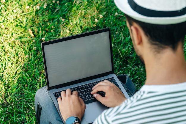 Nicht erkennbarer junger kaukasischer mann mit einem laptop auf dem rasen sitzend