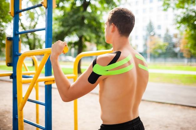 Nicht erkennbarer junger kaukasischer professioneller bodybuilder mit schwarzen und grünen gummibändern auf den schultern, die am sportplatz aufwerfen.