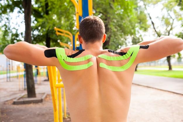 Nicht erkennbarer junger kaukasischer professioneller bodybuilder mit schwarzen und grünen gummibändern auf den schultern, die am sportplatz aufwerfen
