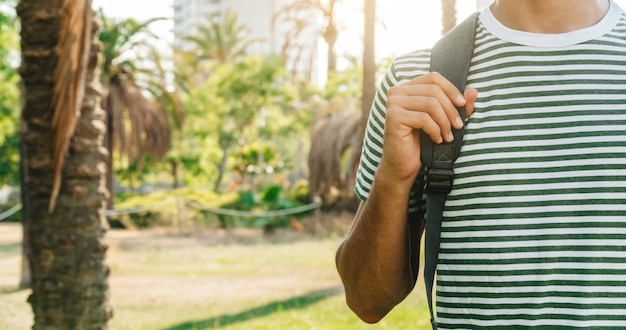 Nicht erkennbarer junger kaukasischer student mit rucksack in einem park