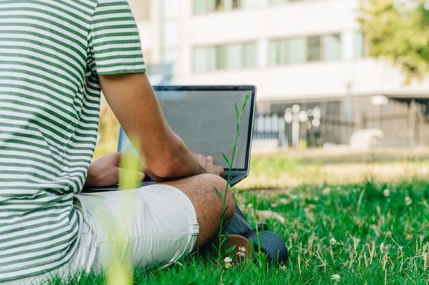 Nicht erkennbarer kaukasischer student mit einem laptop in einem park