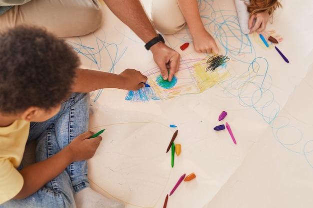 Nicht erkennbarer männlicher lehrer, der mit kindern arbeitet, die bilder zeichnen, während sie spaß in der vorschule oder im entwicklungszentrum haben