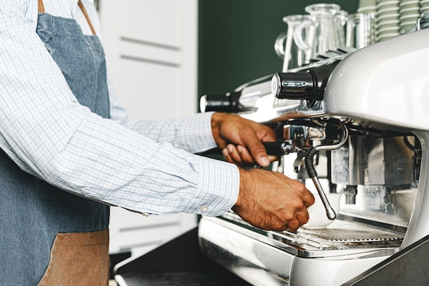 Nicht erkennbarer mann barista, der kaffee auf professioneller kaffeemaschine zubereitet
