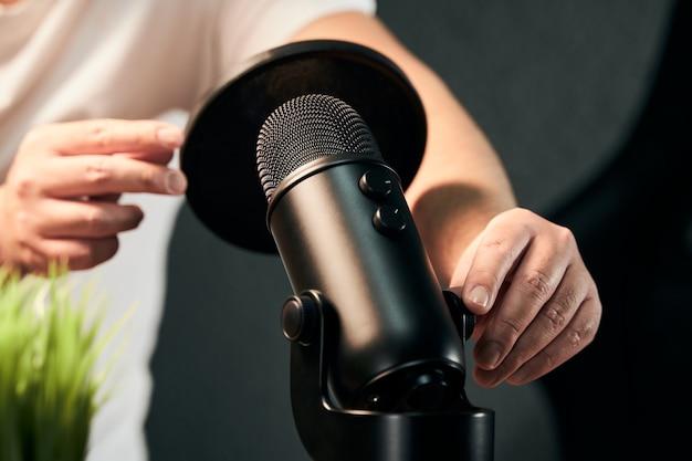 Nicht erkennbarer mann, der eine schwarze mikrofonausrüstung für einen podcast vorbereitet