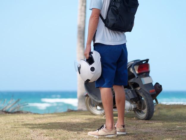 Nicht erkennbarer mann, der helm in der hand hält und mit roller nahe dem ozean steht. reisekonzept.