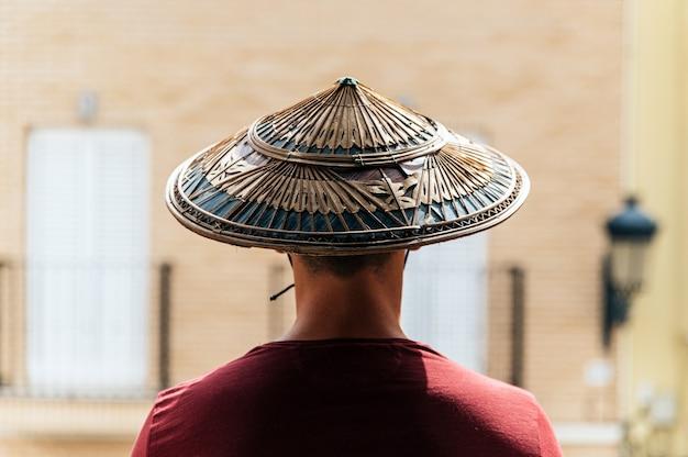 Nicht erkennbarer mann, der vietnamesischen konischen strohhut am sonnigen tag in der stadt trägt und kamera betrachtet
