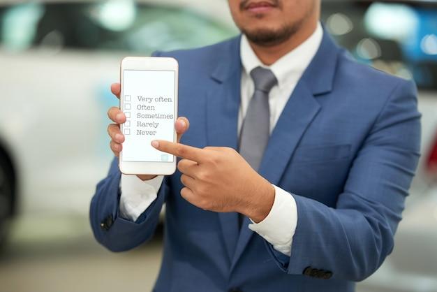 Nicht erkennbarer mann im anzug, der smartphone hält und auf übersicht auf schirm zeigt