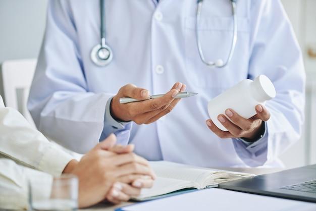 Nicht erkennbarer weiblicher doktor, der dem patienten medikation empfiehlt