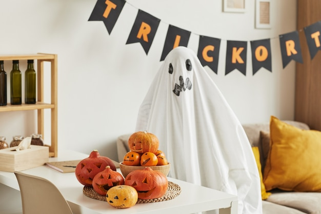 Nicht erkennbares kind, das spaß hat, sich im geisterkostüm im wohnzimmer zu verstecken, das für halloween-partei verziert wird