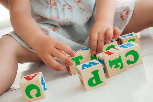 Nicht erkennbares kleines süßes mädchen, das mit abc-würfeln spielt und erzieht. hübsches mädchen, das alphabetblöcke baut. kind, das drinnen spielt.