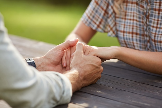 Nicht erkennbares liebendes paar, das hände hält, während es draußen am holztisch sitzt und romantisches date genießt
