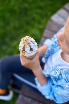 Nicht erkennbares mädchen mit eistüte in der hand, das sich am sommertag im park ausruht, kind, das eis im freien genießt, schöne ferien, sommerzeit summer