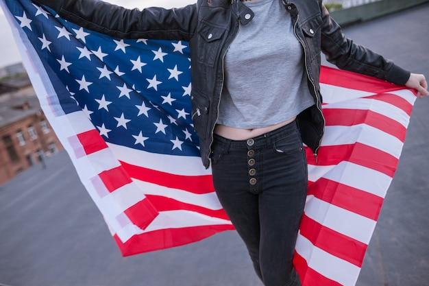 Nicht erkennbares mädchen mit usa-flagge hinter dem rücken auf stadthintergrund. patriot, nationale veranstaltungsfeier, stolz, usa-bürgerkonzept